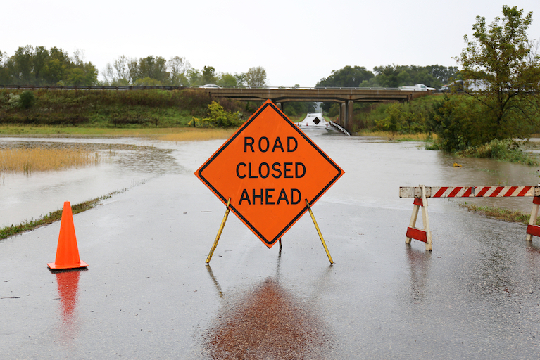 Road Closed Ahead Sign Alongside Traffic Cones Prevents Road Users From Entering a Flooded Roadway