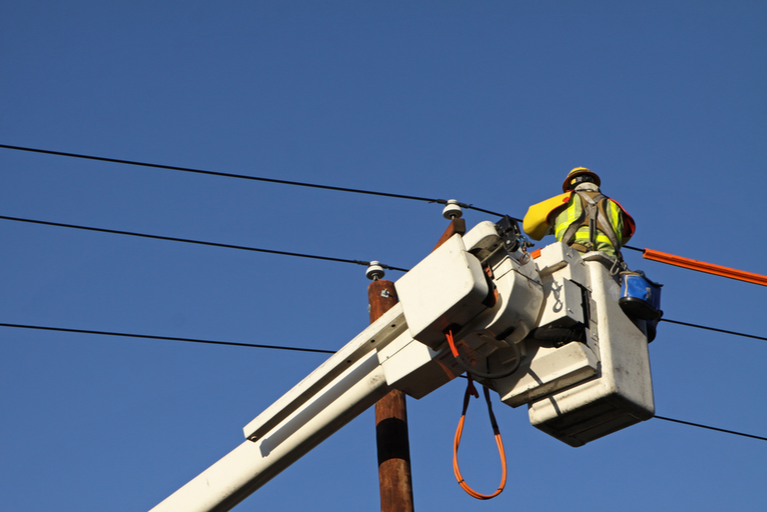 Utility Worker Works on Electric Power Lines